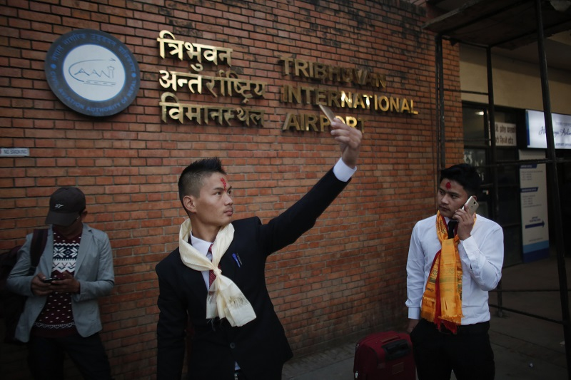 A Nepali Prem Bahadur Ale Magar, 23, takes a selfie in November while he waits for his flight to Malaysia, where he will work in a warehouse as a cleaner, at Tribhuwan International airport in Kathmandu, Nepal. Photo: Niranjan Shrestha / Associated Press