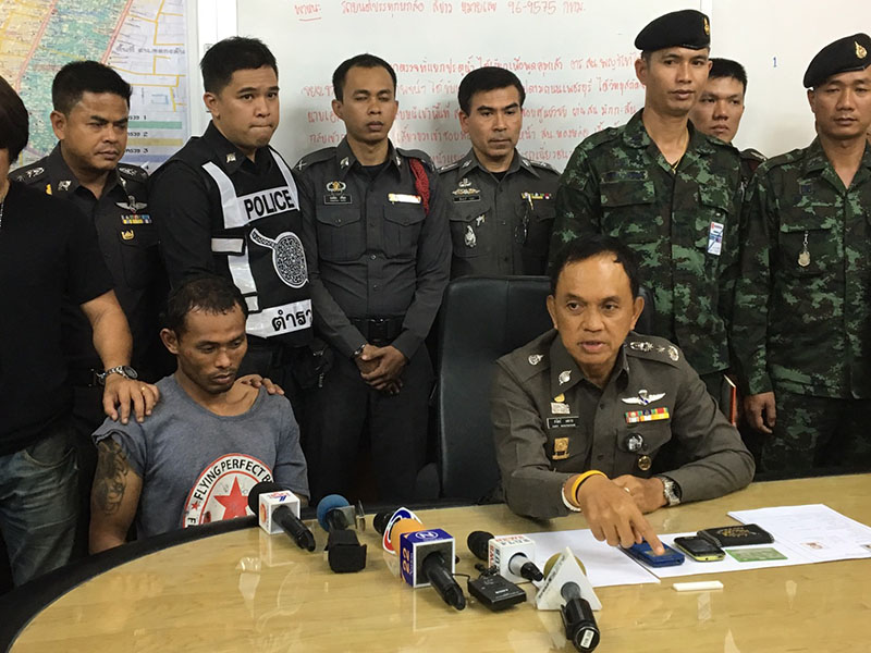 Bangkok police chief Sanit Mahathavorn, seated at right next to the unidentified suspect, speaks to reporters Wednesday afternoon in Bangkok.