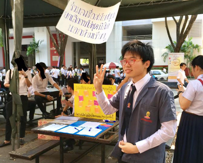Student activist Netiwit Chotiphatphaisal at a petition booth to oppose dress code rules Wednesday. Photo: Pakpoom Joe Thaweesitthichat / Facebook