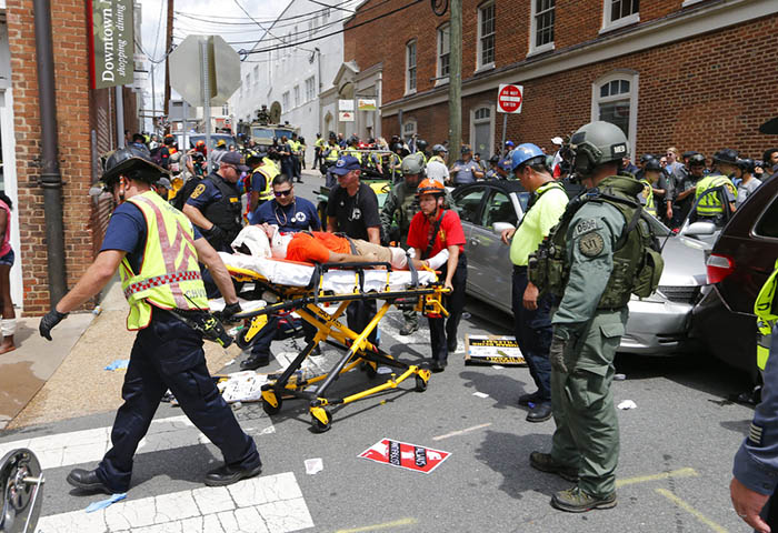 Rescue personnel help injured people after a car ran into a large group of protesters Saturday after a white nationalist rally in Charlottesville. Photo: Steve Helber / Associated Press