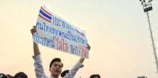 Karn Pongprapaphan holds a sign atop a truck carrying pro-democracy leaders on a march through Bangkok on Saturday.