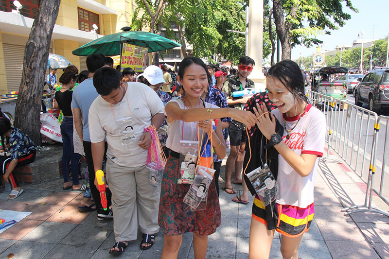 Pro-democracy activists hand out phone covers satirizing junta leader Prayuth Chan-ocha on Ratchadamnoen Avenue.
