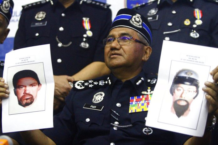 Inspector General of Royal Malaysian Police Mohamad Fuzi Harun shows off two images of suspects of killing of a Palestinian man. Photo: Associated Press