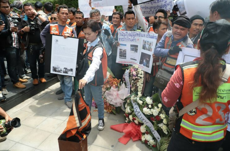 Motorcycle taxis Thursday burn a vest uniform at a protest in front of Grab's Bangkok headquarters.