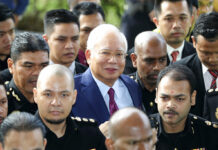 Former Malaysian Prime Minister Najib Razak, center, arrives at a court house Wednesday in Kuala Lumpur, Malaysia. Photo: Vincent Thian / Associated Press