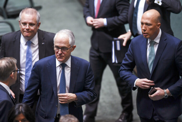 Australian Federal Treasurer Scott Morrison, second left, Prime Minister Malcolm Turnbull, center, and former Home Affairs Minister Peter Dutton, right, leave the chamber at Parliament House in August in Canberra. Photo: Lukas Coch / Associated Press
