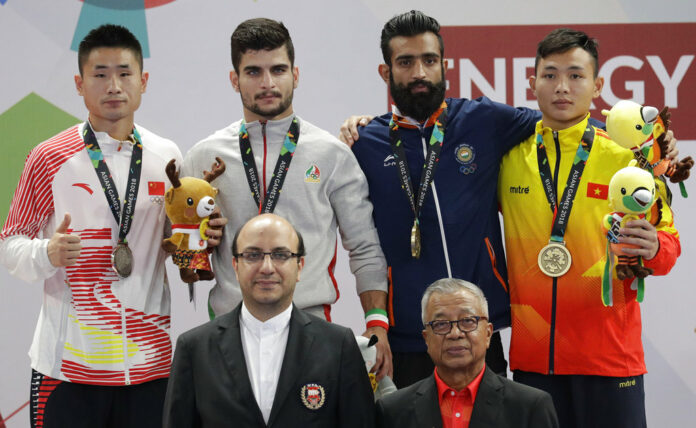 From left, silver medalist China's Xueto Wang, gold medalist Iran's Erfan Ahangarian, bronze medalist India's Surya Singh, and bronze medalist Vietnam's Truong Giang Bui during ceremonies at the wushu men's Sanda 60kg division at the 18th Asian Games on Thursday in Jakarta, Indonesia. Photo: Aaron Favila / Associated Press
