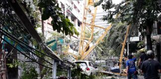 A crane collapsed on a car, trees and electric poles Friday morning in Saladaeng Road.
