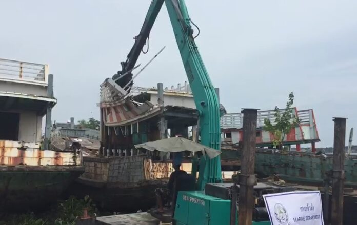 Old fishing boats are being destroyed Wednesday in Samut Sakhon province.