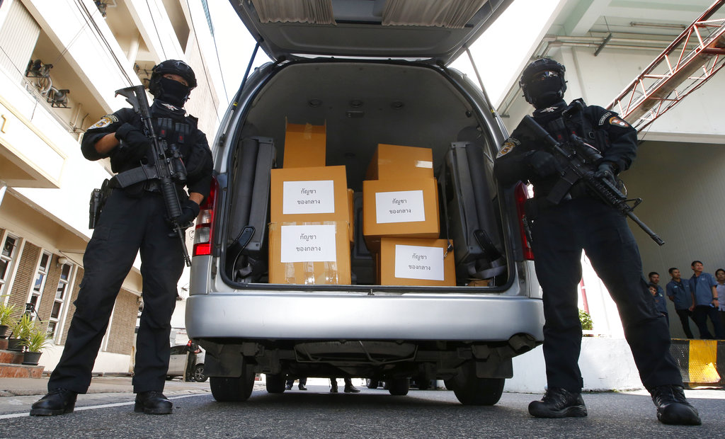 Thai policemen stand guard next to 100 kilograms of seized marijuana before a Tuesday news conference in Bangkok. Photo: Sakchai Lalit / Associated Press