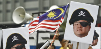 Protesters hold portraits of Jho Low illustrated as a pirate in April during a protest in Kuala Lumpur, Malaysia. Photo: Sadiq Asyraf / Associated Press