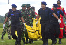 Indonesian soldiers and police officers carry a body bag Friday containing the body of a victim of separatist attack in Nduga district upon its arrival at Moses Kilangin Airport in Timika, Papua province, Indonesia. Photo: Mujiono / Associated Press