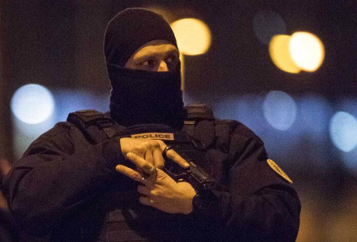 A hooded police officer holds his gun Thursday in Strasbourg, eastern France. Photo: Jean-Francois Badias / Associated Press