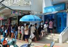 Welfare card holders wait in line Sunday to withdraw 500-baht holiday stipends in Yala province.