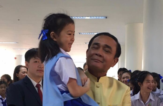 Gen. Prayuth Chan-ocha, right, holds a kindergartner Tuesday in Lampang province.