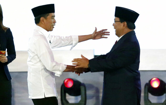 Indonesian President Joko Widodo, left, and his contender Prabowo Subianto, shake hands after a televised debate Thursday in Jakarta, Indonesia. Photo: Tatan Syuflana / Associated Press
