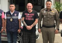 Gary Coughlan, center, stands between two police officers Wednesday on Koh Samui.