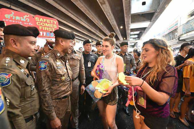 In this undated photo, Lt. Gen. Surachate Hakparn, left, talks to foreigners in Bangkok during the Songkran festivities.