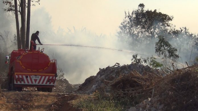 A worker tries to put out forest fire in Phrae province in this undated photo.