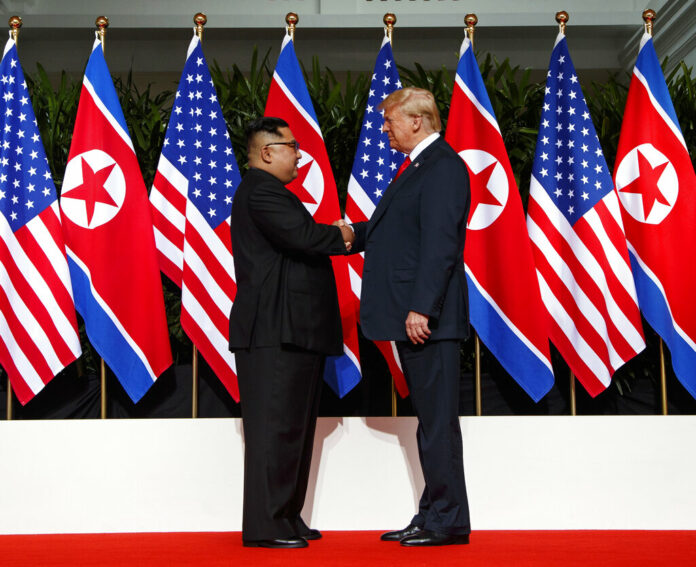 North Korean leader Kim Jong Un, left, and U.S. President Donald Trump shake hands prior to their meeting in June on Sentosa Island in Singapore. Photo: Evan Vucci / Associated Press