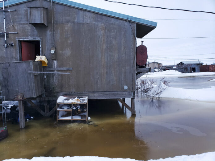 In this Feb. 12, 2019 photo provided by Philomena Keys, high water pushed up the Yukon River from the Bering Sea floods yards around homes in the western village of Kotlik, Alaska. Photo: Philomena Keys via AP