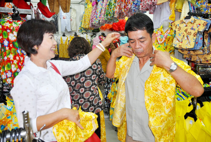 Customers try on yellow Hawaiian shirts at Supak Sawasdee's shop in Korat.