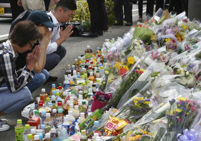People pray for victims at the site where a knife attack took place in Kawasaki near Tokyo Wednesday, May 29, 2019. Photo: Koji Sasahara / AP
