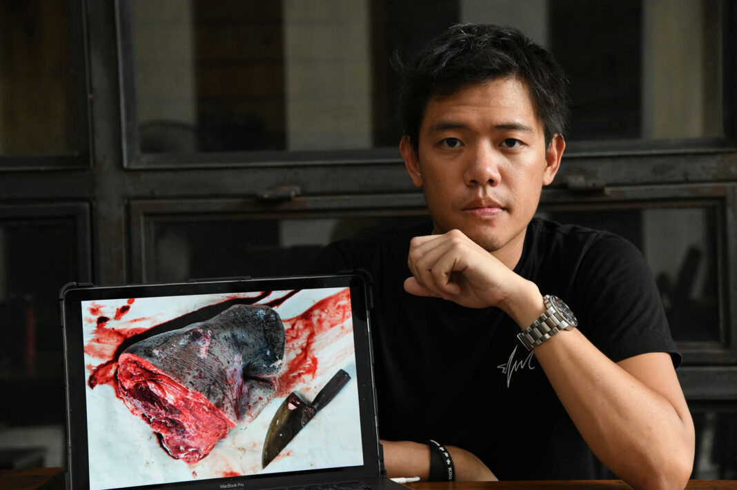Sirachai Arunrugstichai with a photo of a dugong decapitated for an autopsy.