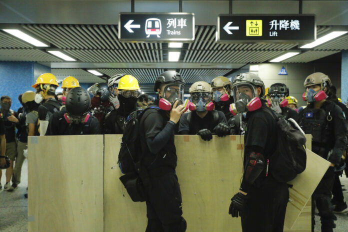 Protesters with makeshift shields pass through a subway station on their way to a police station in Hong Kong on Sunday, Aug. 4, 2019. Photo: Kin Cheung / AP