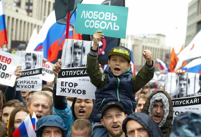 People with posters show portraits of detained protesters and a boy with a poster reads Lyubov Sobol react during a protest in Moscow, Russia, Saturday, Aug. 10, 2019. Tens of thousands of people rallied in central Moscow for the third consecutive weekend to protest the exclusion of opposition and independent candidates from the Russian capital's city council ballot. Photo: Alexander Zemlianichenko / AP