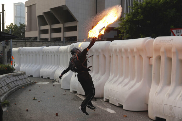 An anti-government protester throws a Molotov cocktail during a demonstration near Central Government Complex in Hong Kong, Sunday, Sept. 15, 2019. Police fired a water cannon and tear gas at protesters who lobbed Molotov cocktails outside the Hong Kong government office complex Sunday, as violence flared anew after thousands of pro-democracy supporters marched through downtown in defiance of a police ban. Photo: Kin Cheung / AP