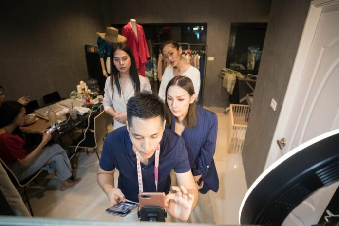 Nunthapong Boonnao (Front) and Manassawee Suangkaew (1st, R) go on live-streaming to promote their online clothing shop registered in Lazada, a major online shopping company in Southeast Asia, at Bangkok, Thailand, Oct. 21, 2019. Photo: Zhang Keren / Xinhua