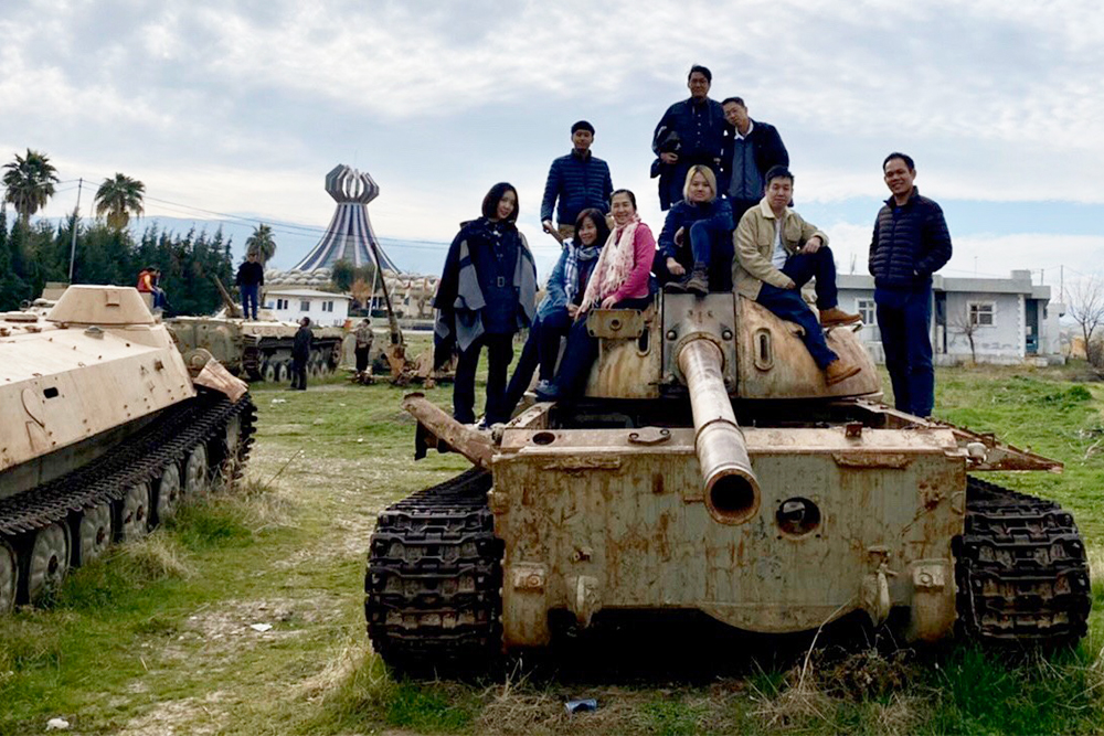 Pongsorn and his tour members pose with a wrecked tank in Iraqi Kurdistan. Photo: Pongsorn Bhumiwat / Courtesy