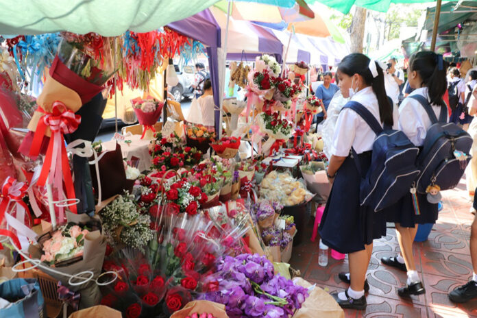 Students shop for bouquets of roses sold at the Flowers Market in Bangkok on Feb. 13, 2020.