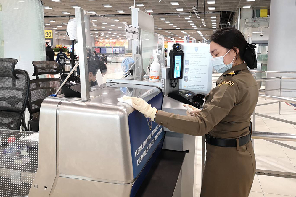 An immigration officer disinfects an immigration desk at Suvarnabhumi Airport on March 11, 2020.