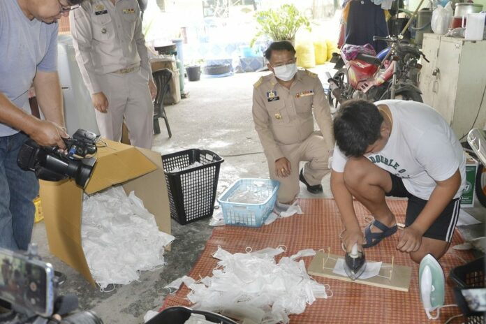 A worker at a shop in Saraburi shows police how he and other employees allegedly wash and iron used face masks for reselling on March 3, 2020.