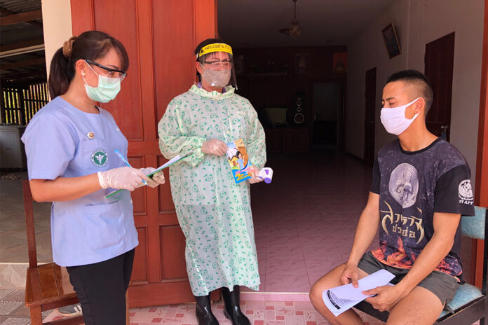 An Aor Sor Mor village health volunteer accompanies a doctor during a house visit in Nong Khai province on May 7, 2020.