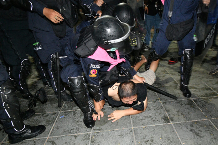 Police arrest a man during a protest at Sanam Luang on Mar. 20, 2021.