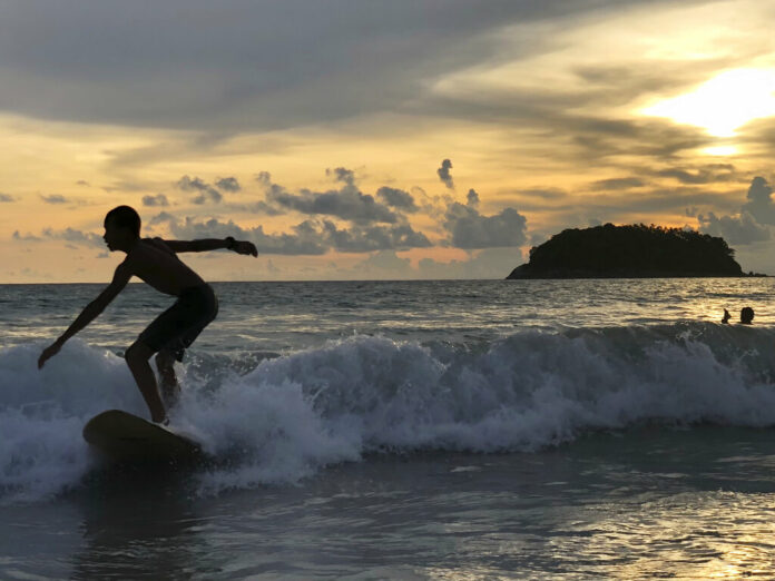 A surfer catches a wave as the sun sets over Kata Beach on the resort island of Phuket, Thailand on Sunday, May 26, 2019. Photo: Adam Schreck / AP